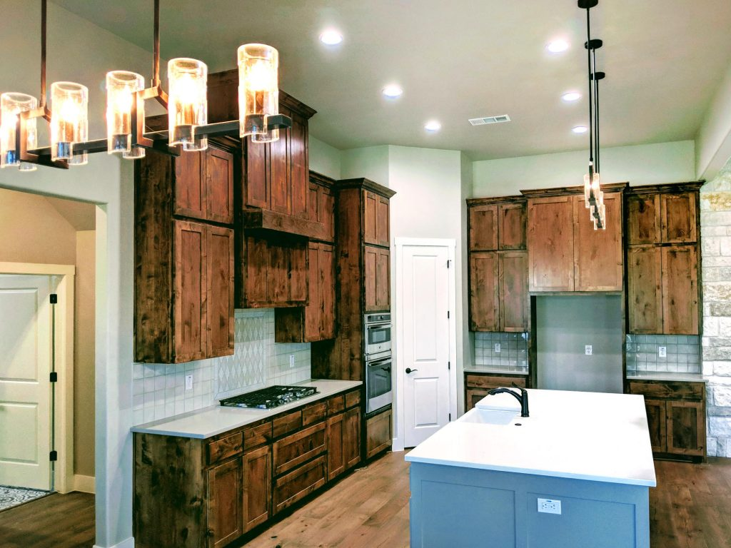 stained wood cabinet with stainless appliances